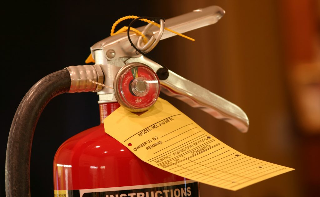 Photo of a fire extinguisher with a blank inspection tag.